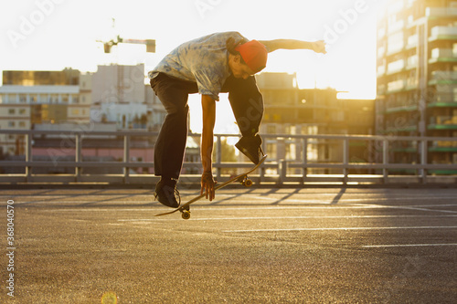 Photo Skateboarder doing a trick at the city's street in summer's sunshine