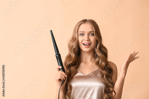 Leinwand Poster Beautiful young woman with curling iron for hair against color background