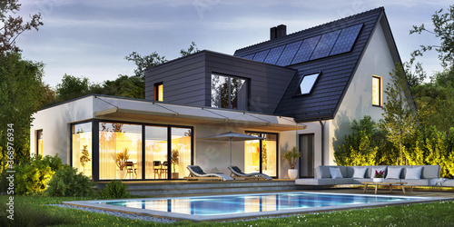 Night view of a beautiful modern house with solar panels and a swimming pool