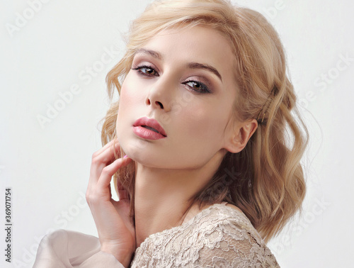 Murais de parede Amazing chic blond beautiful woman with bob curly short hair style and evening makeup posing on gray background