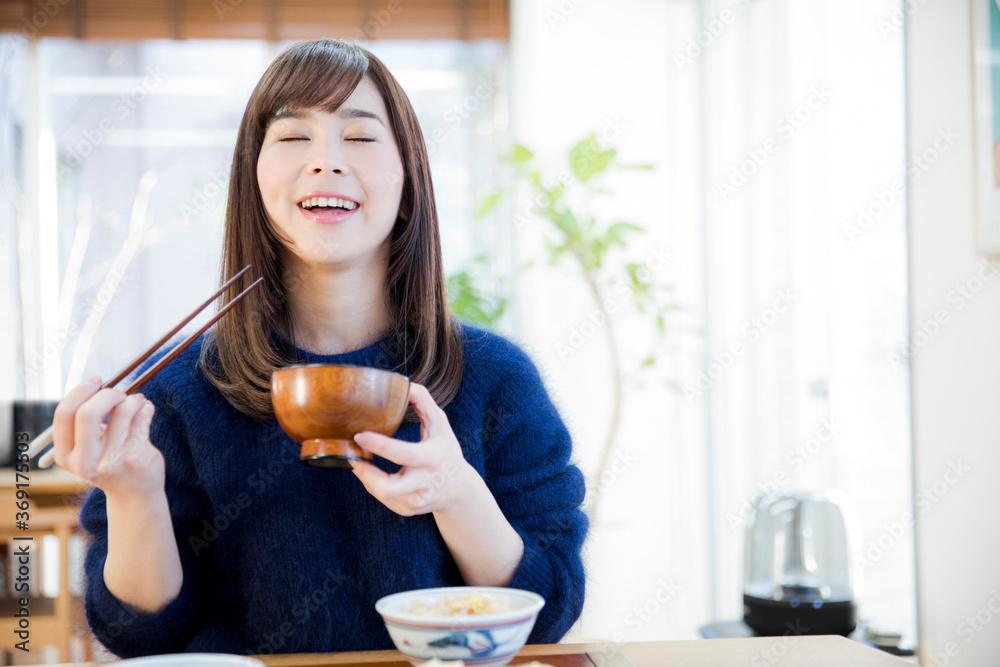 味噌汁を食べる女性