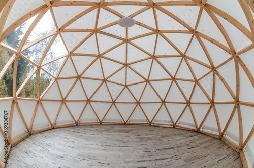 Foto Interior of large geodesic wooden dome tent with window and view to forest