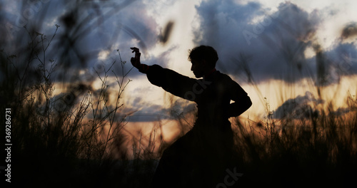 Canvas Print Silhouette of a man practicing martial arts on a sunset. Kung Fu