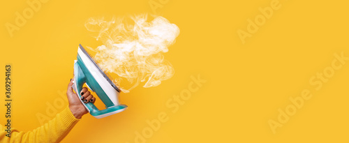 Fotografie, Obraz modern iron with steam in hand over yellow background, panoramic mock-up image