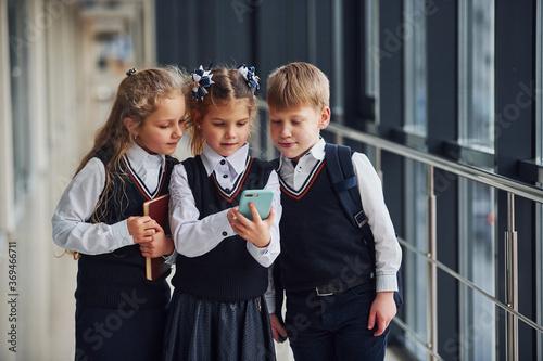 Obraz na plátně School kids in uniform together with phone in corridor