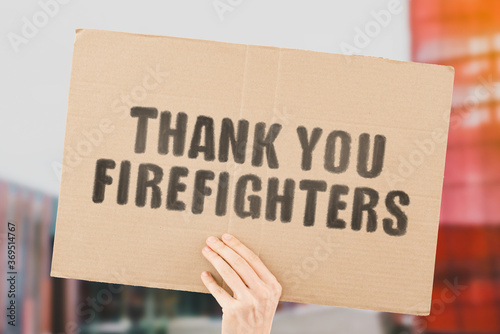Canvas-taulu The phrase  Thank you firefighters  on a banner in men's hand with blurred background