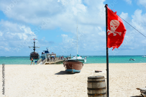 Fotografia Pirate brig at pier on sandy beach with pirate flag