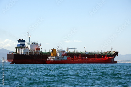 Fotografija A chemical tanker which is anchored being refuelled by a fuel barge at sea