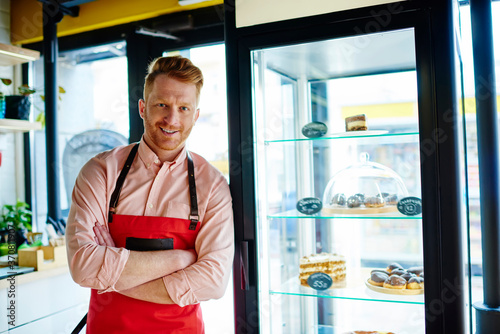 Carta da parati Waiter in apron standing near cake display case and looking at camera