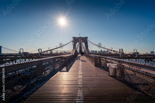 Famous Brooklyn bridge over river against clear blue sky with bright sun in New Fototapeta