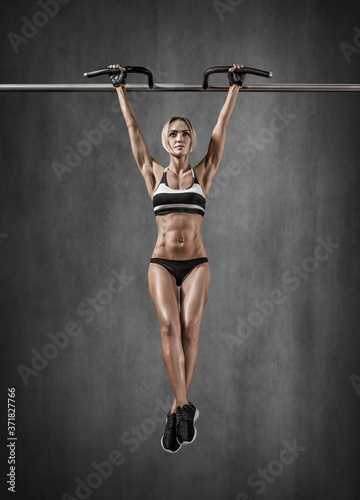 Canvas Print young fitness woman chin-up on horizontal bar