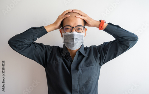 Fototapeta Asian businessman having headache and stressed while wearing surgical mask whole day in covid-19 pandemic