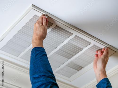 Fotografija Man opening ceiling air vent to replace dirty HVAC air filter
