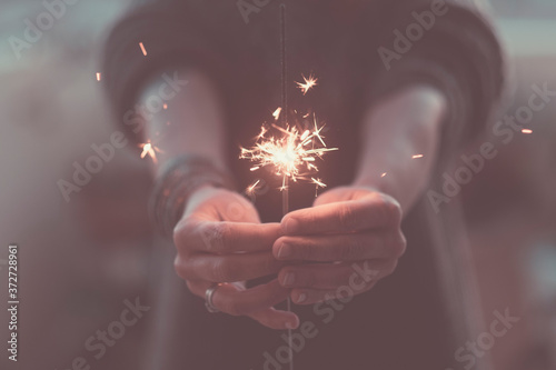 Fotografia Romantic love concept of life with close up of hands with fire sparklers by nigh