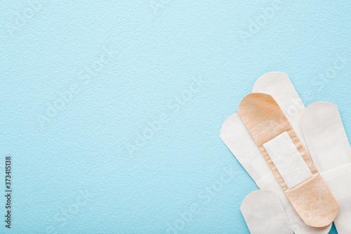 Leinwand Poster New adhesive bandages on light blue table background