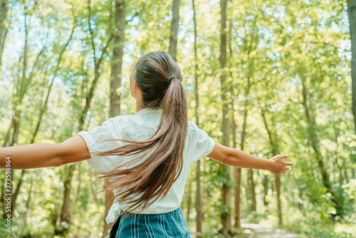 Slika na platnu Happy woman in forest with open arms from behind breathing clean air