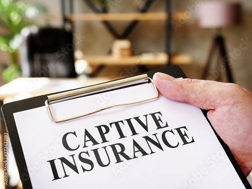 Foto Hand holds documents Captive insurance about insurance.