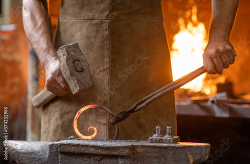 Fotografía Close up blacksmith is processing a hot metal object of a spiral shape at anvil