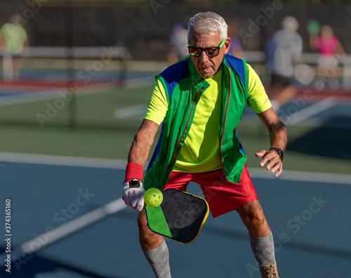 Senior man hitting a pickleball with paddle Fototapet