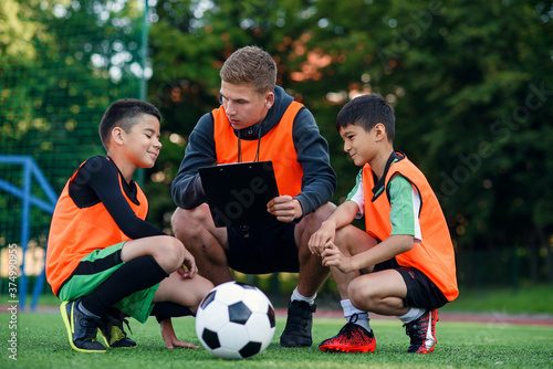 Professional soccer coach tells the strategy of football game to his attentive teen players at stadium during training Fototapete