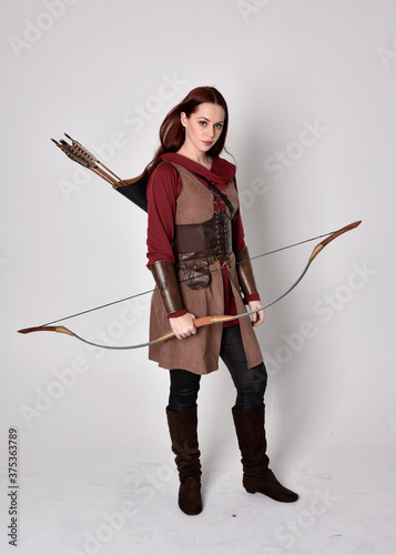 Canvas Print Full length portrait of girl with red hair wearing  brown medieval archer costume