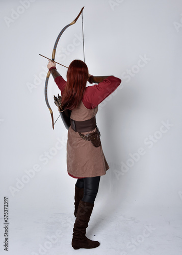 Obraz na płótnie Full length portrait of girl with red hair wearing  brown medieval archer costume