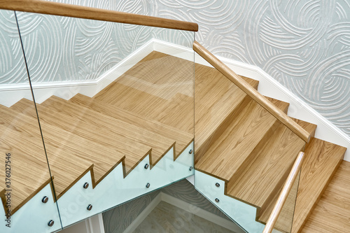 Canvas Print Wooden staircase with glass railings and wooden handrail