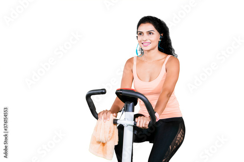 Obraz na plátně Woman hears music and working out on exercise bike