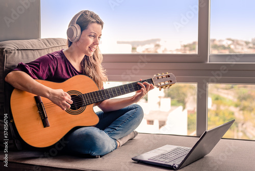 Fotografia Woman learning online how to play guitar