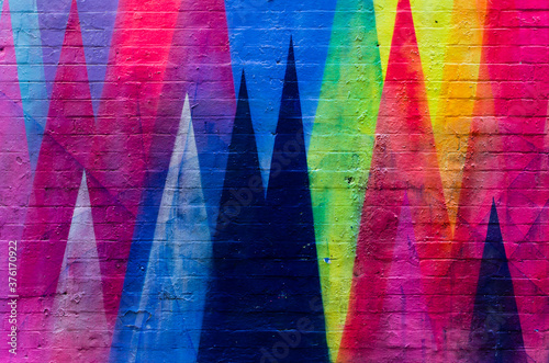 Brick wall painted in vibrant colors with geometric figures