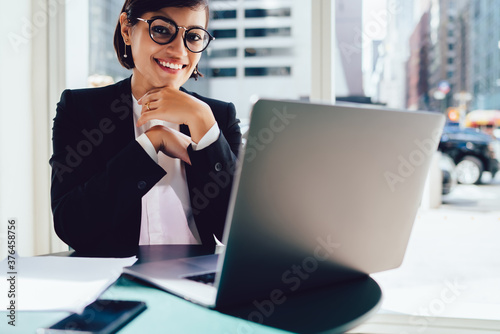 Leinwand Poster Smiling woman in glasses with laptop in modern workplace