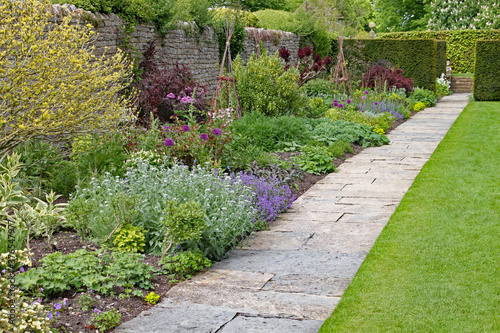 Fotografiet Stone flag path in front of a herbaceous border at an English country garden