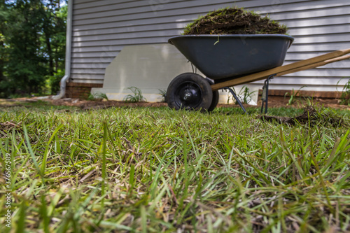 Fotografija Low angle shot of centipede grass and a wheelbarrow full of sod beside a buildin
