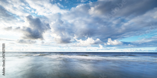 Fotografie, Obraz Clear sky with lots of glowing cumulus clouds above the Baltic sea shore after thunderstorm at sunset