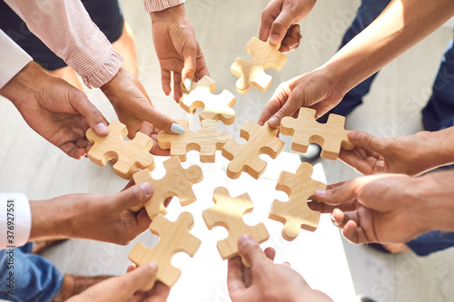 Fotografia Company employees playing game and joining pieces of jigsaw puzzle during team b