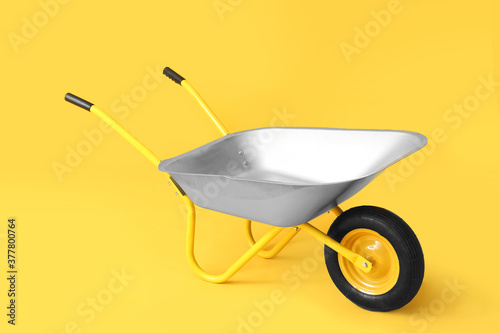 Billede på lærred Empty wheelbarrow on color background