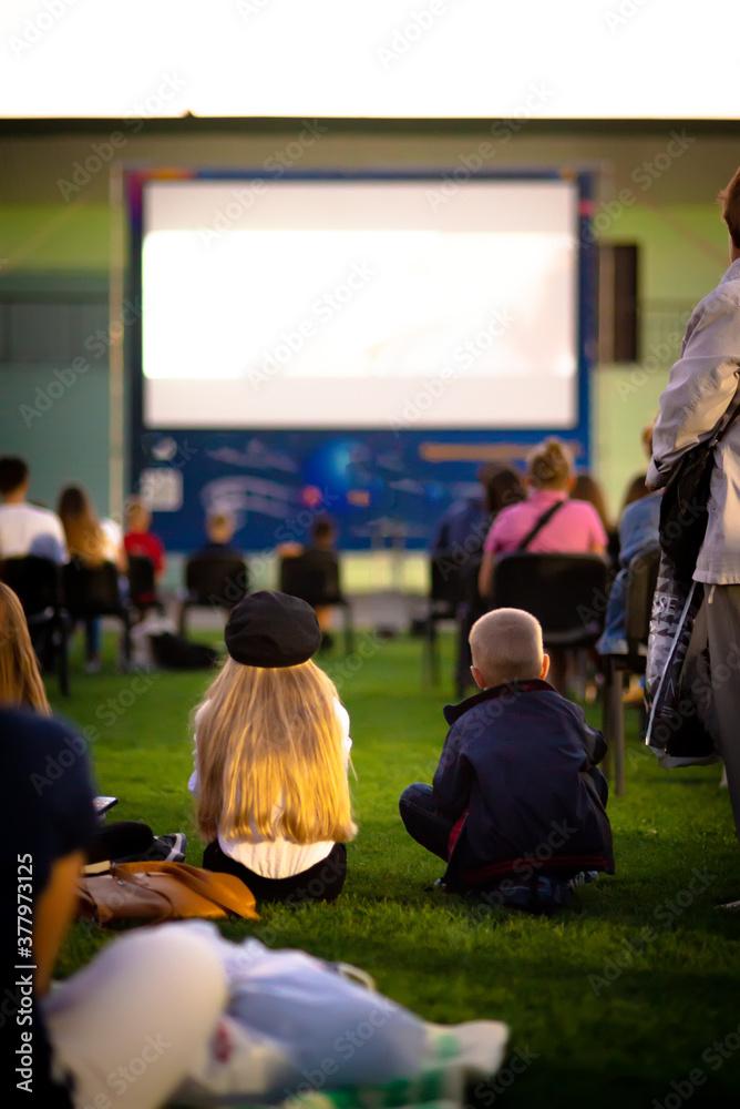 Summer cinema. Children watching a movie on the screen of a summer cinema