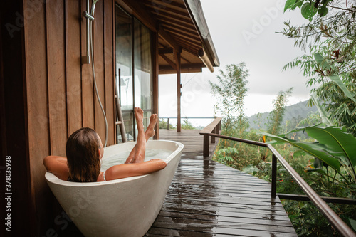 Wallpaper Mural Back view woman pampering her body in water while lie in bath tube outdoor with