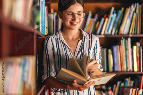 Young smiling attractive college girl leaning on book shelves in library and searching for material for homework Fototapete