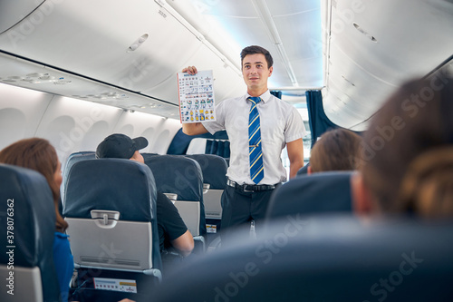 Photo Handsome man holding safety information list to flight take off
