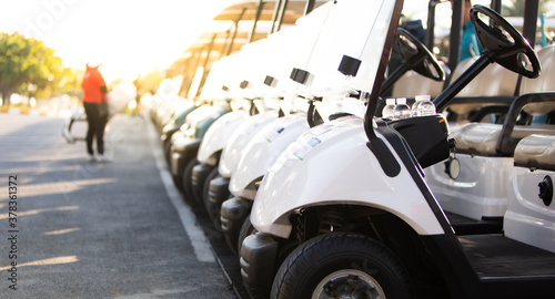 row of golf carts on a golf course. golf course carts cars at luxury resort sport venue in neat line row.