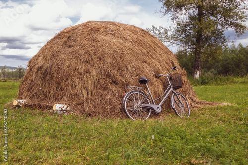 Fotografiet Bicycle in a field near a haystack