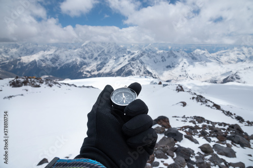 Fotografiet Magnetic compass in a man's hand in a glove against the background of the snow-capped mountains of the caucasus in the afternoon