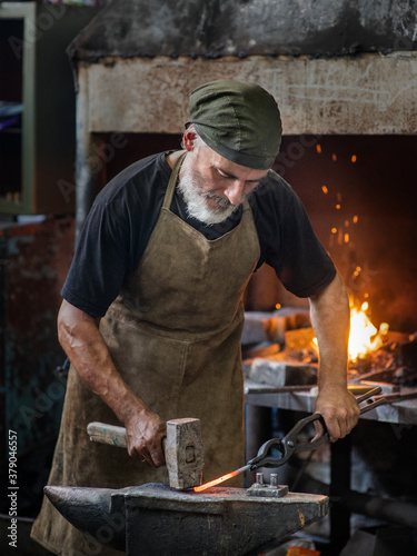 Photo Old blacksmith working metal with hammer on the anvil in the forge