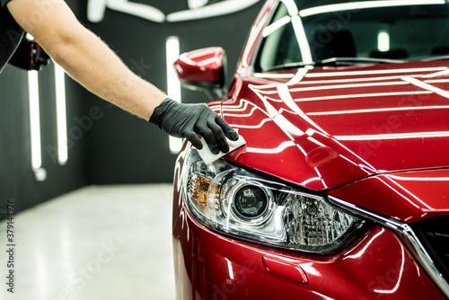 Valokuvatapetti Car service worker applying nano coating on a car detail.