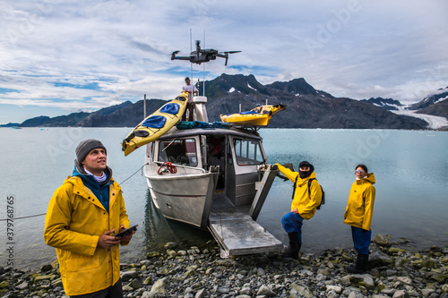Stampa su Tela Man with crew members from scientific expedition  send a drone near the vessel d
