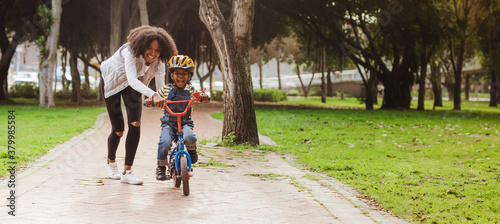 Photo Little boy learning to ride bicycle at park with mother