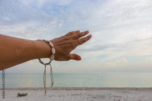 Murais de parede Girl hand touching the sky on calm sea background