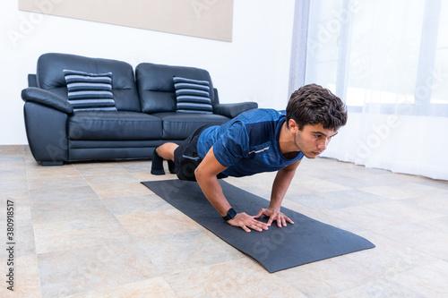 Chico joven haciendo flexiones en casa con smartwach Fotobehang