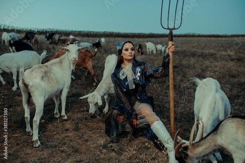 Woman farmer stands with pitchfork among a herd of goats. Fototapet